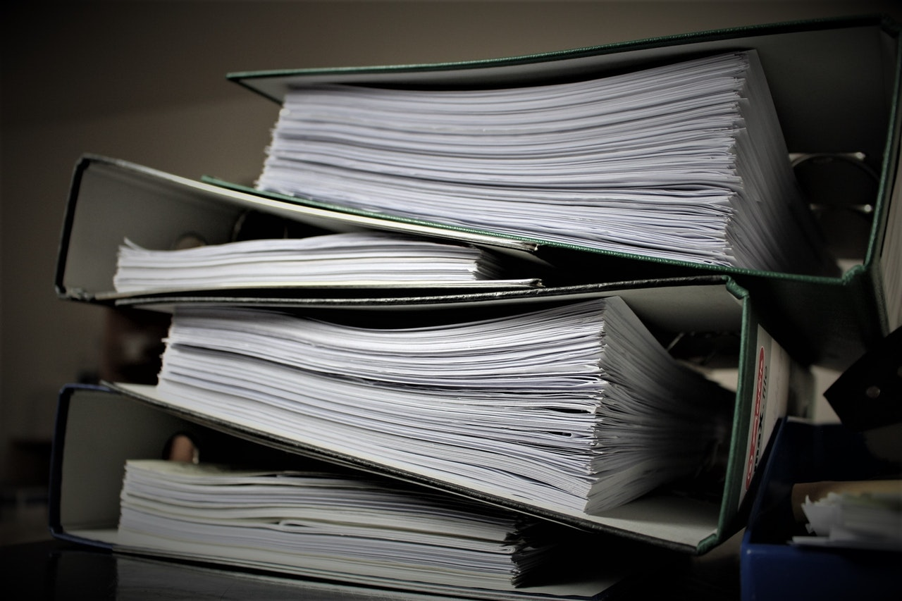 Large, paper filled binders, stacked on top of each other.